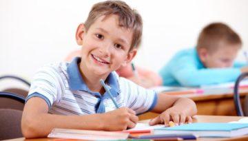 Criança escrevendo em inglês, mostrando forte desenvolvimento infantil.