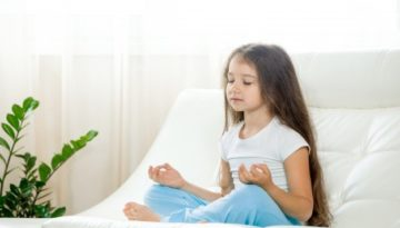 Criança meditando para diminuir indisciplina