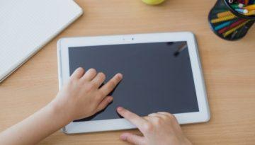 Aluno em contato com tecnologia em sala de aula.