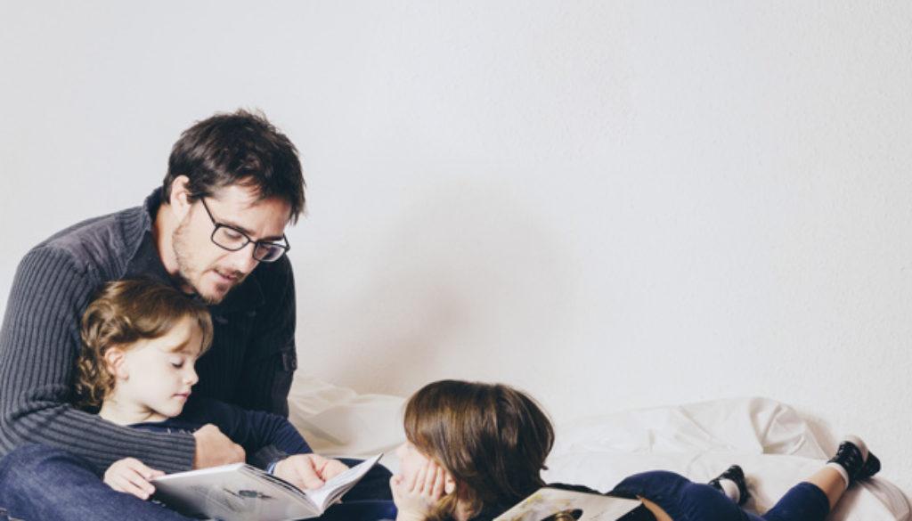 Pai lendo para os filhos após aula de como incentivar a leitura em casa