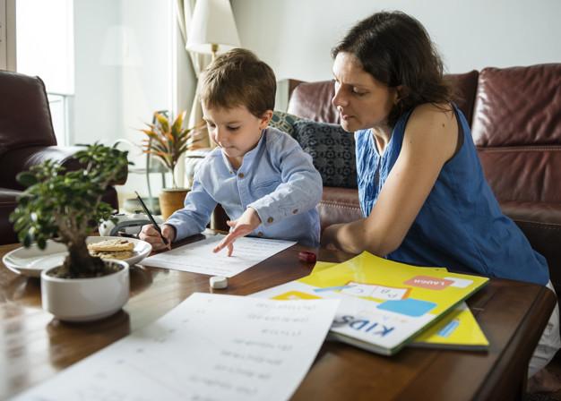 Mãe ensina o filho em casa, dentro da proposta educacional homeschooling.