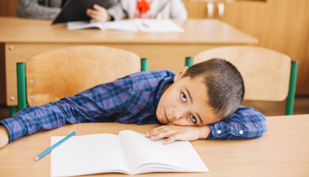 menino-estudante-apoiando-se-escrivaninha-em-sala-aula_23-2147885343