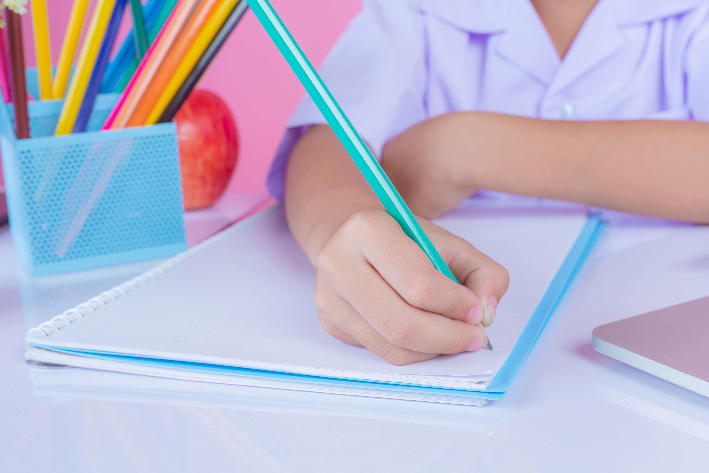 Criança desenvolve uma das atividades de escrita para educação infantil em sala de aula