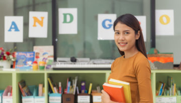 Professora na escola segurando livros.