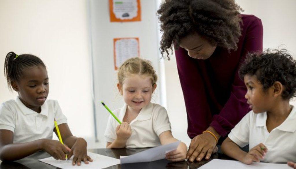Professora desenvolvendo ação de combate ao preconceito racial na escola