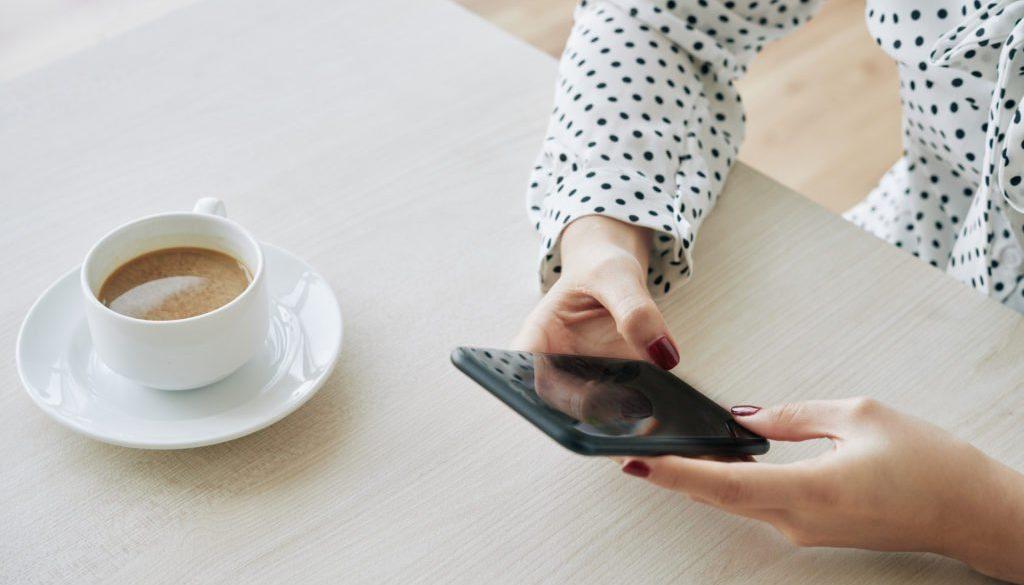Coordenadora pedagógica lendo novidades de educação no celular e tomando café