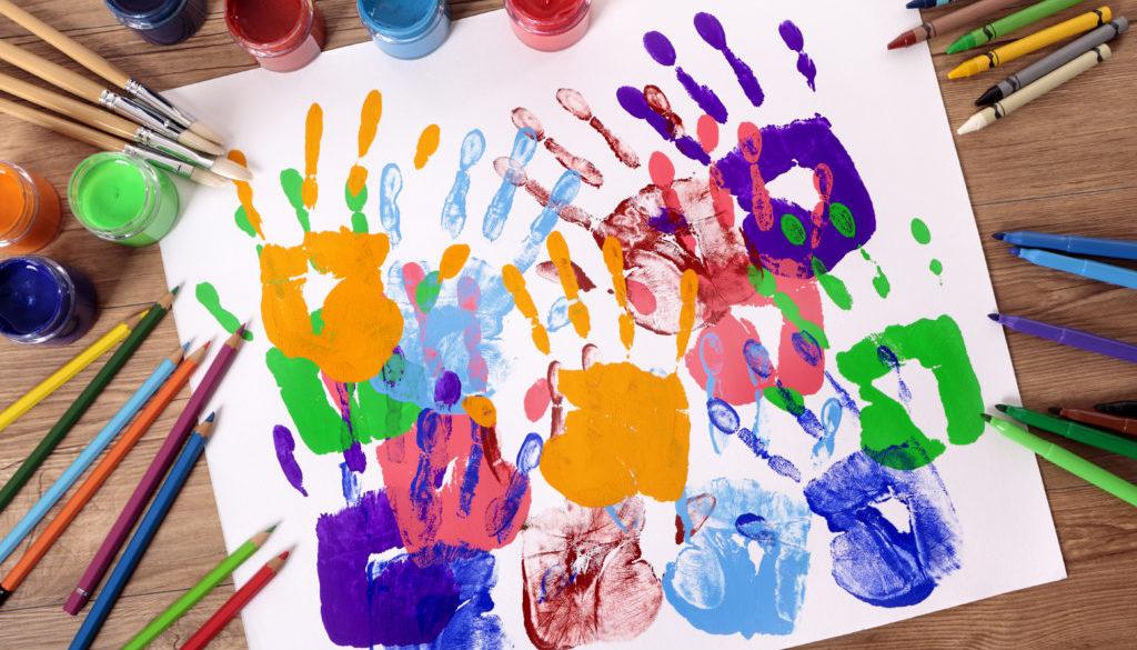 Mãos de criança pintadas em um projeto lúdico na educação infantil