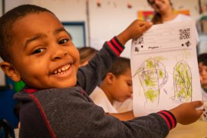 Aluno cria sua própria história infantil durante a aula no projeto da Estante Mágica.